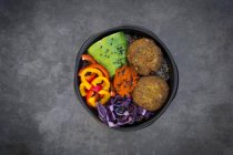 Lunch bowl of quinoa, red cabbage, bell pepper, avocado, quinoa fritters, ajvar and black sesame — Stock Photo