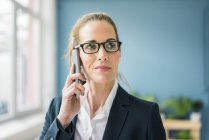 Successful businesswoman standing at home, talking on the phone — Stock Photo