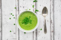Bowl of pea soup, spoon and peas on wood — стоковое фото