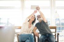 Счастливая зрелая пара сидит на стульях дома с помощью планшета — стоковое фото
