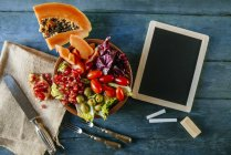 Papaya salad, pomegranate, lettuce, tomato, olives and endive with slate, on blue wood — Stock Photo