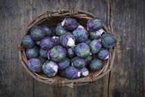 Purple brussels sprouts in basket on rustic wooden table — Foto stock