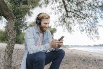 Улыбающийся мужчина в наушниках с помощью смартфона на пляже — стоковое фото