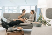 Couple relaxing on couch at home and having breakfast — Stock Photo