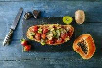 Половина папайи украшена кусочками банана, киви и клубники на тарелке с лантом — стоковое фото