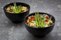Bowl of vegan Pad Thai with mini green asparagus and tofu, chili, spring onion, peanut and coriander — Stock Photo