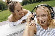Две счастливые девушки в наушниках на улице — стоковое фото