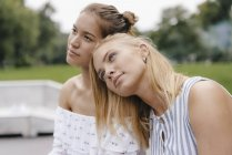 Молодая женщина отдыхает на плече подруги — стоковое фото