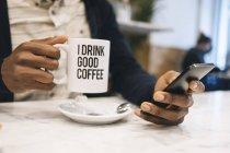 Nahaufnahme eines Mannes mit einer Tasse Kaffee in einem Café mit dem Handy — Stockfoto