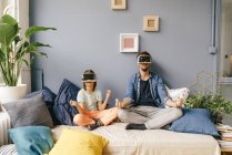 Father and son wearing VR glasses and practicing yoga at home — Stock Photo