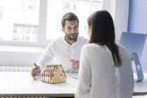 Мужчина объясняет архитектурную модель женщине — стоковое фото