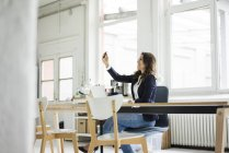Laughing businesswoman sitting at desk in loft and taking selfie — Stock Photo