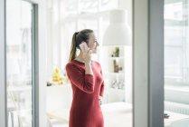 Mulher sorridente ao telefone olhando pela janela — Fotografia de Stock