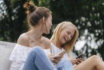 Dos mujeres jóvenes riendo con teléfonos celulares al aire libre - foto de stock