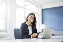 Портрет счастливой деловой женщины, сидящей за столом в офисе — стоковое фото