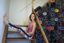Расслабленная зрелая женщина на лестнице рядом с ассортиментом ковриков для йоги — стоковое фото