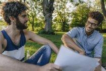Два мультикультурному друзі сидять у парку і обговорювати документи — стокове фото