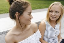Zwei lächelnde junge Frauen, die im Freien sprechen — Stockfoto