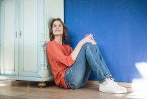 Femme détendue assise sur le sol à la maison — Photo de stock