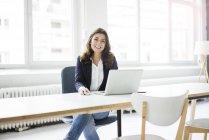 Портрет счастливой деловой женщины, сидящей за столом в офисе и работающей на ноутбуке — стоковое фото