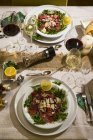 Beef carpaccio on rocket on festive laid table — Stock Photo
