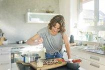 Femme fabriquant du chocolat aux fraises dans la cuisine à la maison — Photo de stock