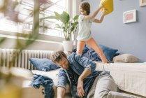 Padre e hijo teniendo pelea de almohadas en casa - foto de stock