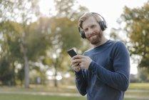 Ritratto di uomo sorridente con cellulare che ascolta musica con cuffie in un parco — Foto stock