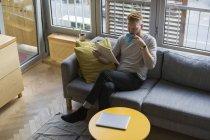 Homem sentado no sofá em casa lendo jornal e bebendo café — Fotografia de Stock