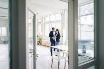 Homme d'affaires et femme d'affaires partageant un téléphone portable au bureau — Photo de stock
