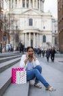 Reino Unido, Londres, mujer con bolsas de la compra en el teléfono celular sentado en las escaleras de la ciudad - foto de stock
