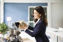 Donna d'affari che riempie i chicchi di caffè in macchina da caffè espresso — Foto stock