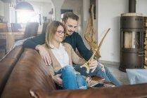 Lächelndes Paar auf der heimischen Couch mit Tablet und Eiffelturm-Modell — Stockfoto