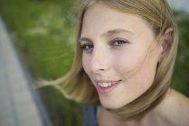 Porträt einer lächelnden jungen Frau, die in die Kamera blickt — Stockfoto