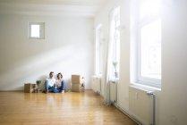 Pareja madura sentada en el suelo en habitación vacía junto a cajas de cartón y utilizando la tableta - foto de stock