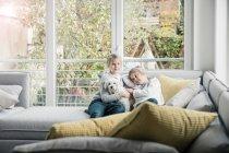 Портрет двух девушек с собакой на диване в гостиной — стоковое фото