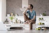 Улыбающийся человек, сидящий на кухонном прилавке и смотрящий на расстояние — стоковое фото