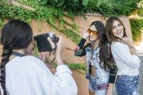 Giovane donna scattare foto dei suoi amici con la macchina fotografica — Foto stock