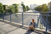 Young woman sitting on bridge and listening music with headphones — Stock Photo