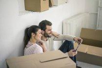 Pareja sentada en un nuevo hogar rodeada de cajas de cartón mirando a la tableta - foto de stock