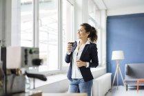 Felice donna d'affari con un bicchiere di caffè in soppalco guardando fuori dalla finestra — Foto stock