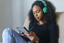 Портрет молодой женщины, сидящей в кресле, слушающей музыку в наушниках и планшете — стоковое фото