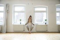 Femme mûre dans une pièce vide debout à la fenêtre — Photo de stock