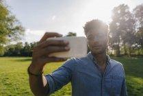 Jeune homme afro-américain tenant un téléphone portable dans le parc au coucher du soleil — Photo de stock