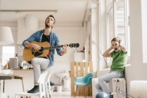 Horrified son covering his ears with father playing guitar at home — Stock Photo