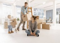 Счастливая семья переезжает в новый дом с отцом и дочерью, несущими картонные коробки — стоковое фото