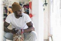 Улыбающийся африканский американец с баскетбольным мячом, смартфоном и наушниками — стоковое фото