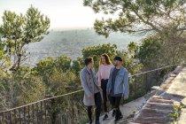 Três amigos subindo uma colina — Fotografia de Stock
