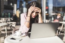 Разочарованная молодая деловая женщина использует ноутбук в кафе на открытом воздухе — стоковое фото