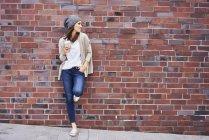 Jeune femme avec du café pour aller penché au mur de briques — Photo de stock